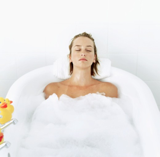 high angle view of a young woman lying in a bathtub with her eyes closed : Stock Photo