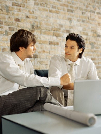 two businessmen sitting in front of a laptop and discussing work in an office : Stock Photo