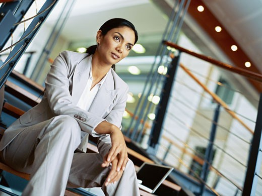 Stock Photo: 1491R-1092963 businesswoman sitting on stairs with a laptop beside her in an office