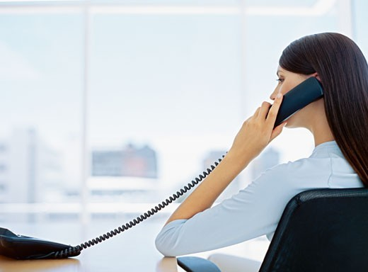 rear view of a businesswoman talking on a telephone in an office : Stock Photo