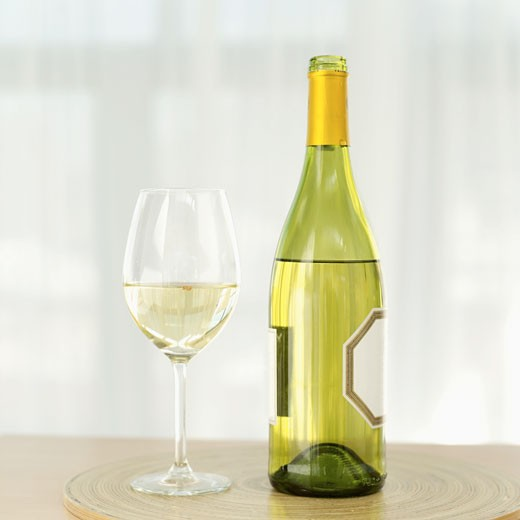 close-up of a bottle of white wine with a wineglass on a table : Stock Photo