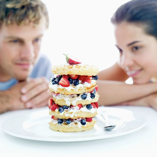 young couple looking at a tower of fruit filled waffle tarts : Stock Photo
