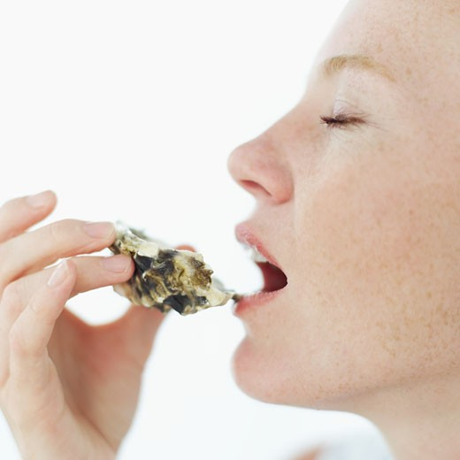 side profile of a young woman eating an oyster from the shell : Stock Photo