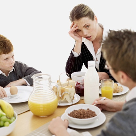 Stock Photo: 1491R-1093785 mid adult woman sitting with her two sons at the breakfast table