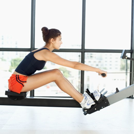 side profile of a young woman exercising on a rowing machine in a gym : Stock Photo