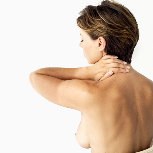 rear view of a naked mid adult woman with her hand on her neck : Stock Photo