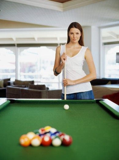Portrait of a young woman standing near a pool table holding a cue stick : Stock Photo