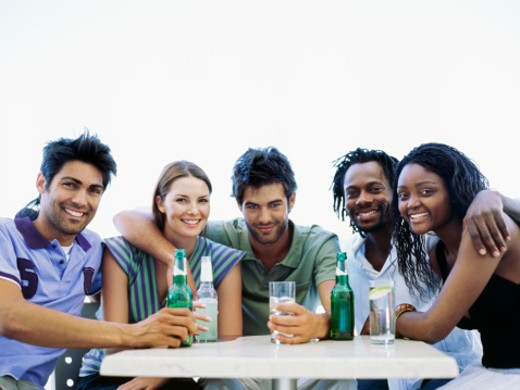 Stock Photo: 1491R-1094935 Portrait of five young people sitting at a table