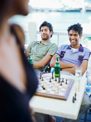 Portrait of two young men sitting in front of a chessboard smiling : Stock Photo