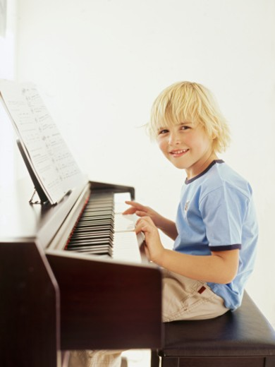 Side profile of a boy playing the piano : Stock Photo