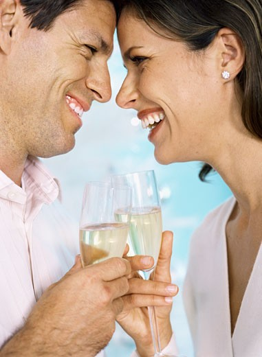 Side profile of a mid adult couple holding champagne flutes and toasting : Stock Photo