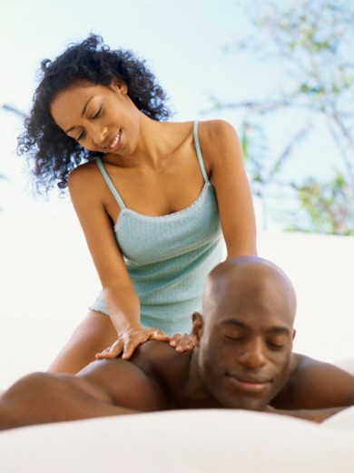 Mid adult woman giving a back massage to a man : Stock Photo