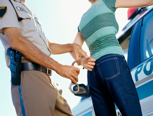 Mid section view of a policeman arresting a young woman : Stock Photo