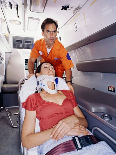 Stock Photo: 1491R-1095845 Paramedic carrying an injured woman into the ambulance