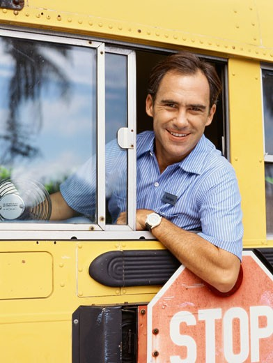 Stock Photo: 1491R-1095961 Portrait of a bus driver smiling and looking out the window