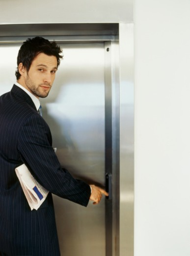 Portrait of a businessman using an elevator : Stock Photo