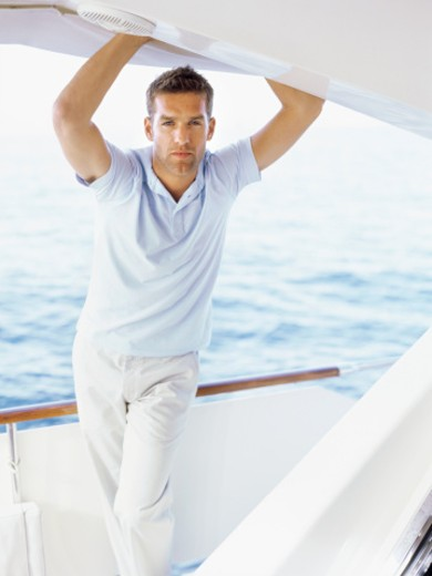 Portrait of a young man standing on a motorboat with his arm raised : Stock Photo