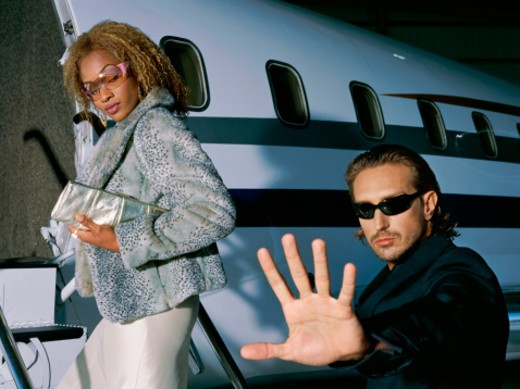 Close-up of two people entering a private jet : Stock Photo