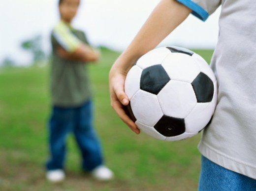 Stock Photo: 1491R-1096979 Close-up view of a football held by a child