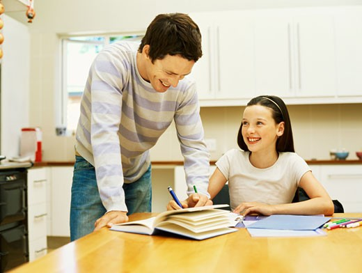 Stock Photo: 1491R-1097033 Father helping his daughter with her homework
