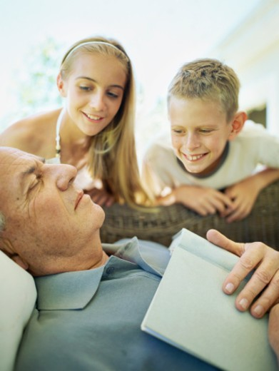 Stock Photo: 1491R-1097132 Grandchildren looking at their sleeping grandfather