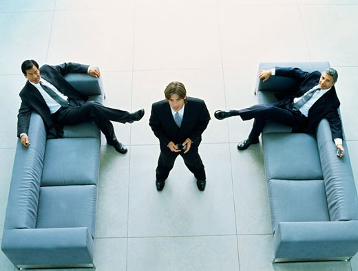Stock Photo: 1491R-1097328 High angle view of two businessmen sitting on sofas with another standing between them