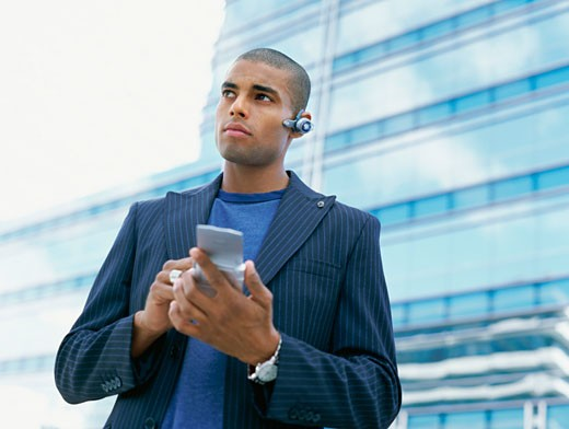 Stock Photo: 1491R-1097473 Low angle view of a young man holding a palm top computer