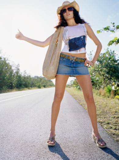 Stock Photo: 1491R-1097498 Low angle view of a young woman hitchhiking