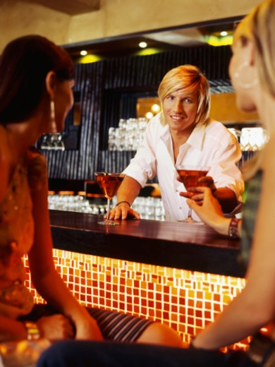 Stock Photo: 1491R-1098464 Bartender serving drink to a young women