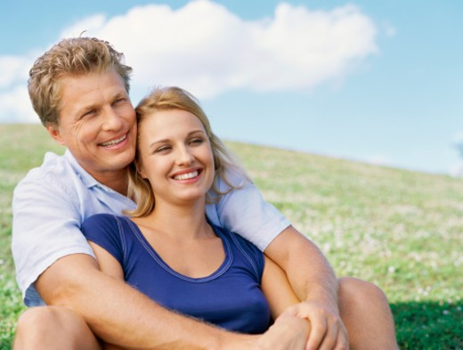 Close up of mid adult couple sitting on the grass and smiling : Stock Photo
