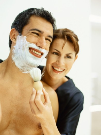 Close-up of a mid adult woman applying shaving cream on a mid adult man's face : Stock Photo