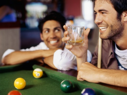 Close-up of a young man holding a  glass and a pool stick : Stock Photo