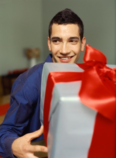 Close-up of a young man holding a gift and smiling : Stock Photo