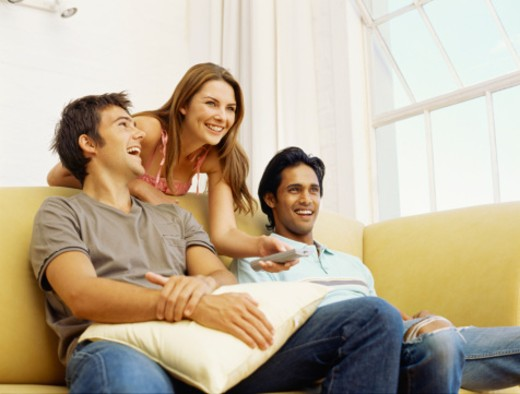 Young woman standing holding a remote control with two Young men sitting on a sofa : Stock Photo