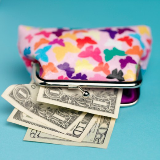 Close-up of purse with dollars sticking out : Stock Photo