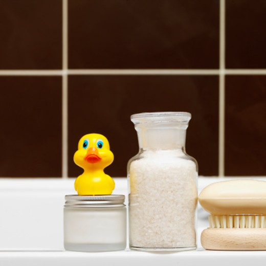 Close-up of toiletries and rubber duck on side of bath : Stock Photo