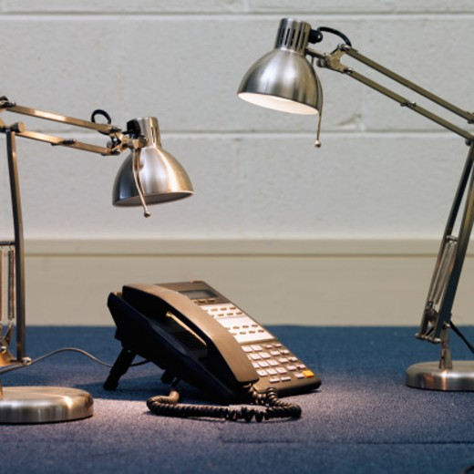 Close-up of two desk lamps shining light on telephone : Stock Photo