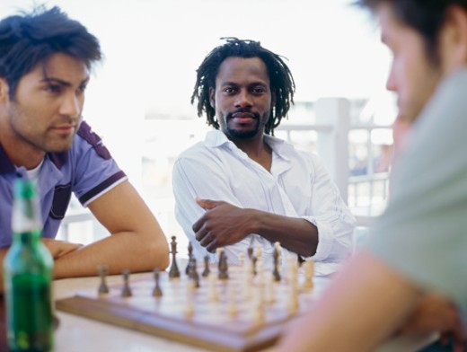 Three young men playing chess : Stock Photo