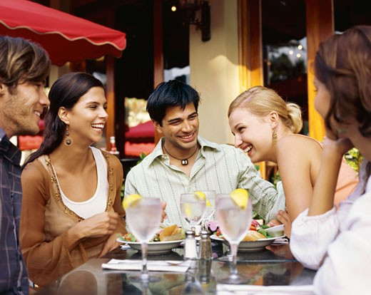 Two young men and three young women sitting around a restaurant table : Stock Photo