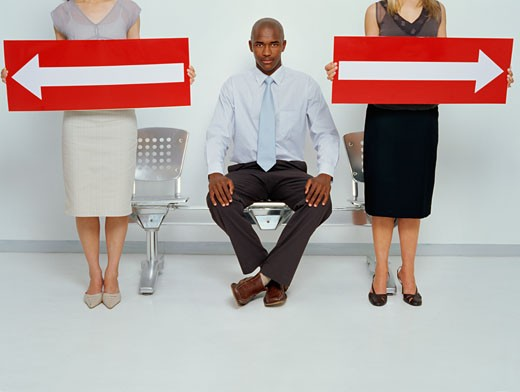 Two young women holding arrow signs with a young man sitting on a chair beside them : Stock Photo