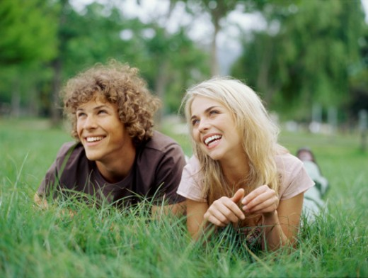Stock Photo: 1491R-1100787 Young couple lying on the grass
