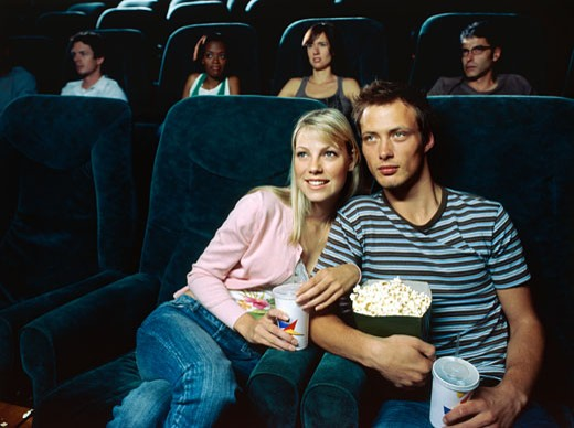 Stock Photo: 1491R-1100838 Young couple watching movie in a movie theatre