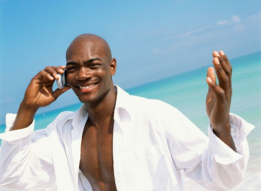 Young man walking on the beach and talking on a mobile phone : Stock Photo