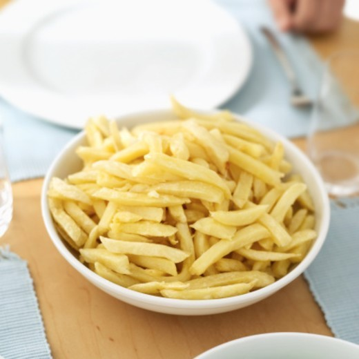 Close-up of a bowl of French fries on a table : Stock Photo