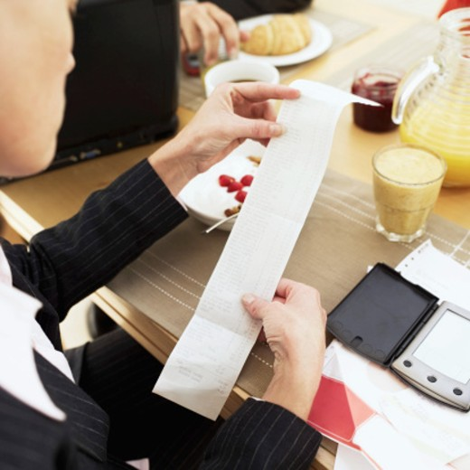 Businesswoman sitting at a breakfast table holding a bill : Stock Photo