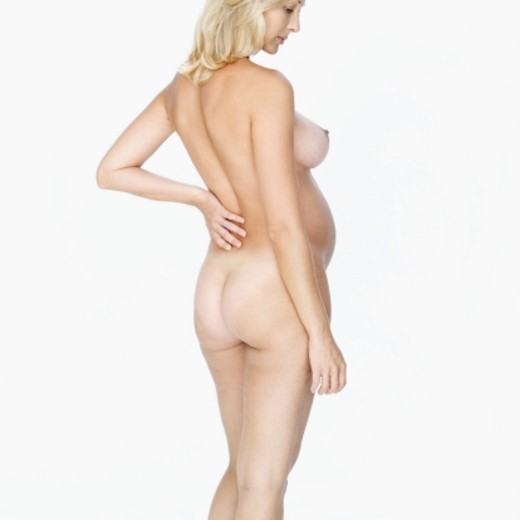 Rear view of a young nude pregnant woman standing with hand on her back : Stock Photo