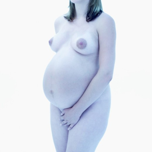 Stock Photo: 1491R-1101471 Young nude pregnant woman standing with hand in the front of her