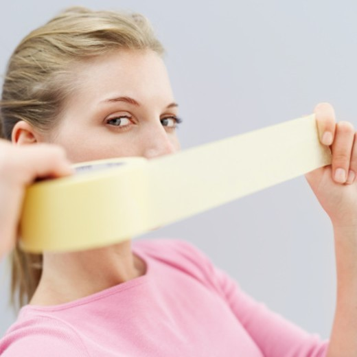 Stock Photo: 1491R-1101731 Portrait of a young woman holding a length of masking tape