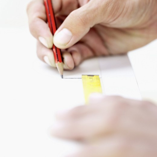 Stock Photo: 1491R-1101861 Close-up of hands drawing a line with a measuring tape on paper
