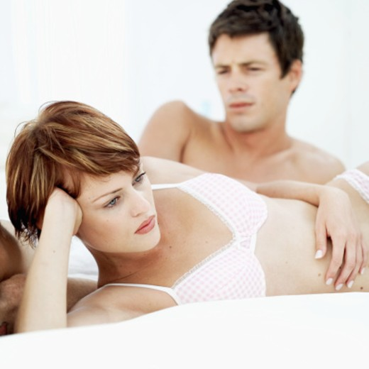 Young woman lying on bed in her underwear with a young man lying next to her : Stock Photo